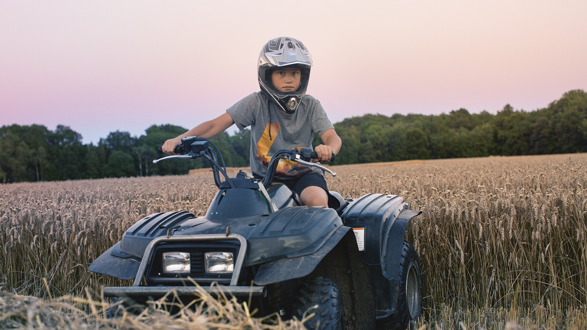 Pojke sitter på fyrhjuling på ett sädesfält i solnedgång
