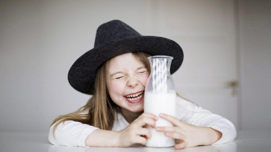 Flicka med hatt skrattar och håller i en flaska mjölk