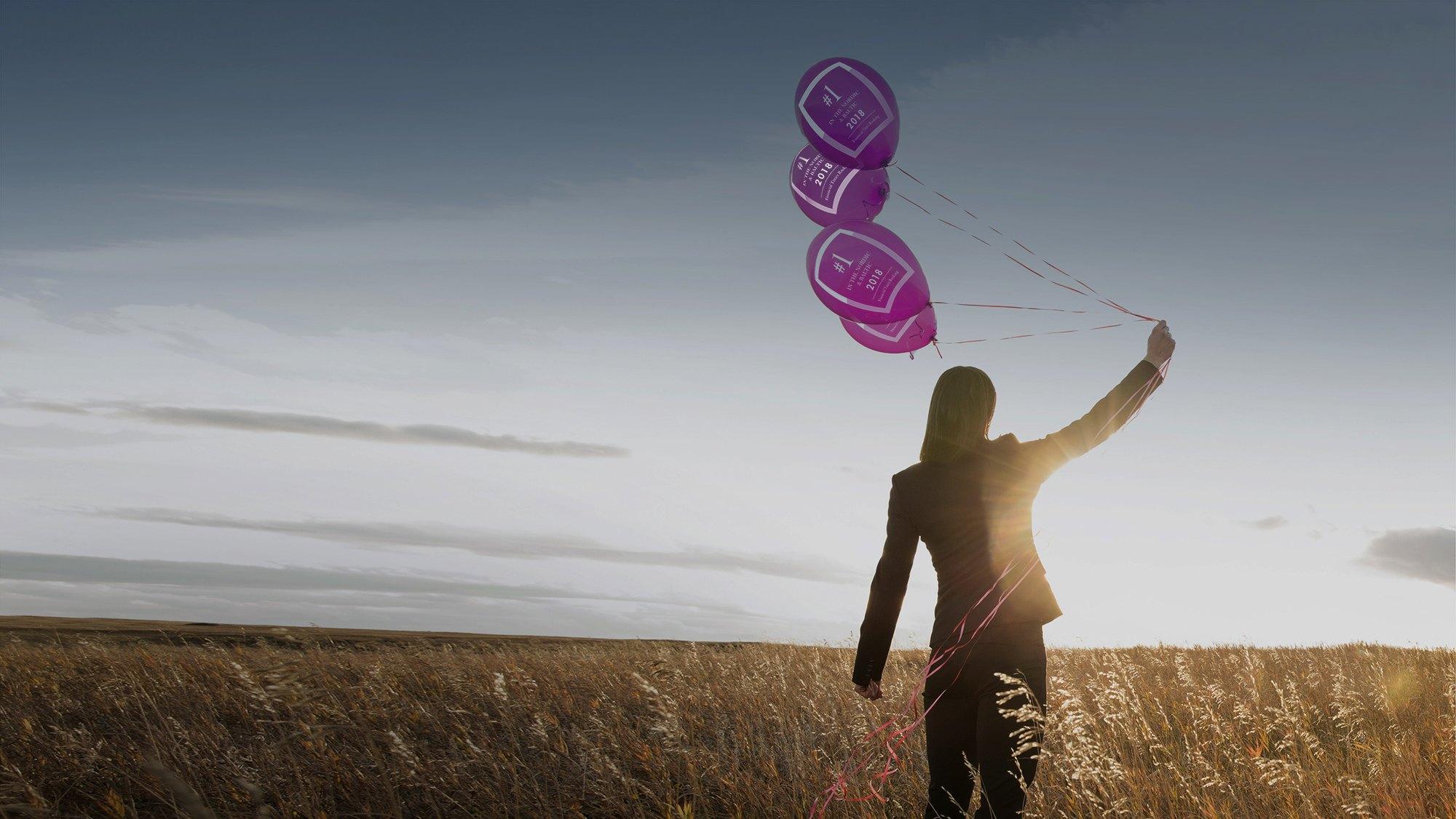 Kvinna står med lilla ballonger i handen på ett sädesfält i solnedgången